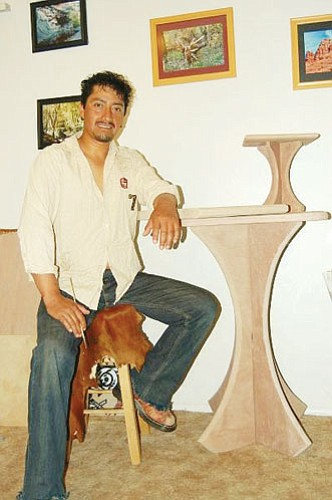 <br>Photo/Autumn Tax<br> Efrain Tax sits at one of his tables to paint a memorial stone in the Arizona Flagstone Creations home office.