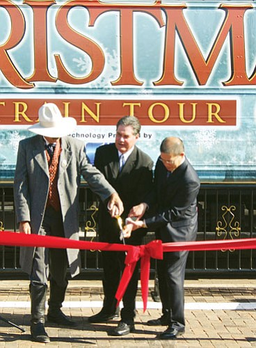 Pictured (from left to right) is Williams Mayor John Moore, Bob Gault, vice president of Walt Disney Motion Pictures Studios special events, and David Lim, chief marketing officer for Amtrak, as they cut the ribbon at the opening of the May Christmas event.