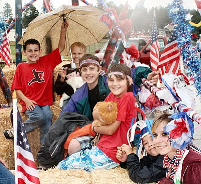 Scott Warren/Scott's Pics, Photos and Portraits Parade participants brave the rain during last year's July 4 parade in downtown Williams.