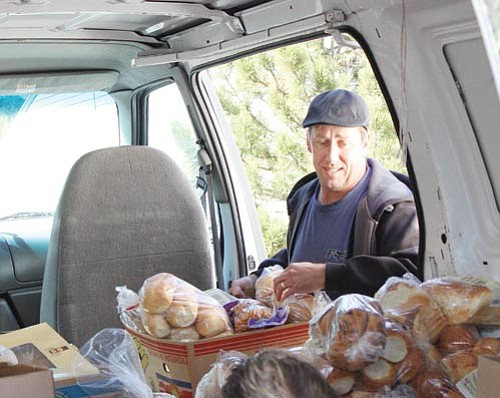 <br>Ryan Williams/WGCN<br> Williams Food Bank Director Guy Mikkelsen unloads a van full of bread and rolls. The Food Bank feeds approximately 180 families per month on Friday afternoons.