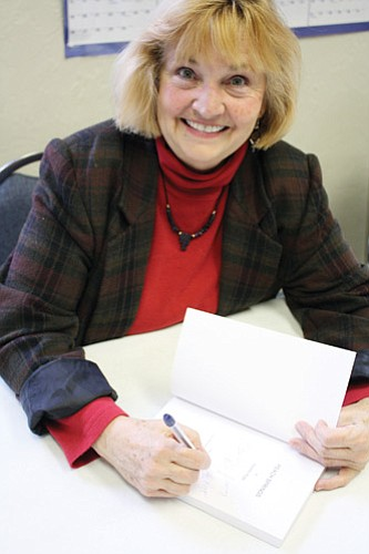 Patrick Whitehurst/WGCN Local author Cosette Riggs signs a copy of her book, 'Peach Springs.'
