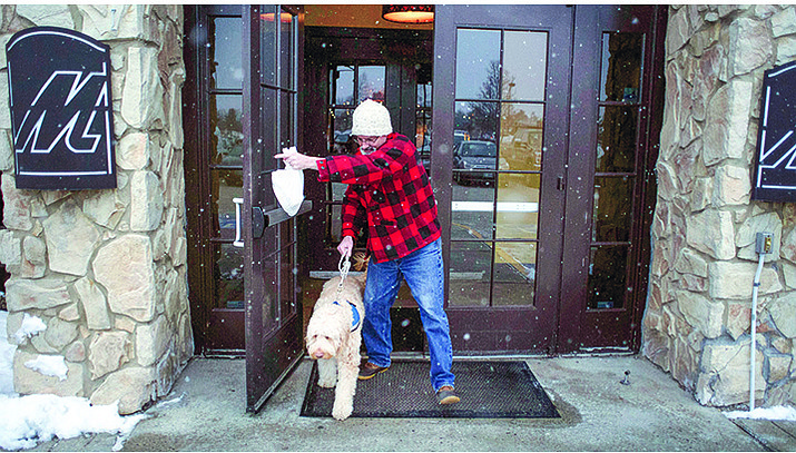 "Sean McDonough leaves Macaroni Grill in South Portland, Maine, Monday, Feb. 8, after eating lunch with his service dog, Bruno, at his side. McDonough suffered brain injuries in a car crash in 2008 and depends on Bruno to keep him calm in public settings. ""Businesses are so fed up with the fakes that those of us with legitimate service dogs are being scrutinized and discriminated against,"" McDonough said.