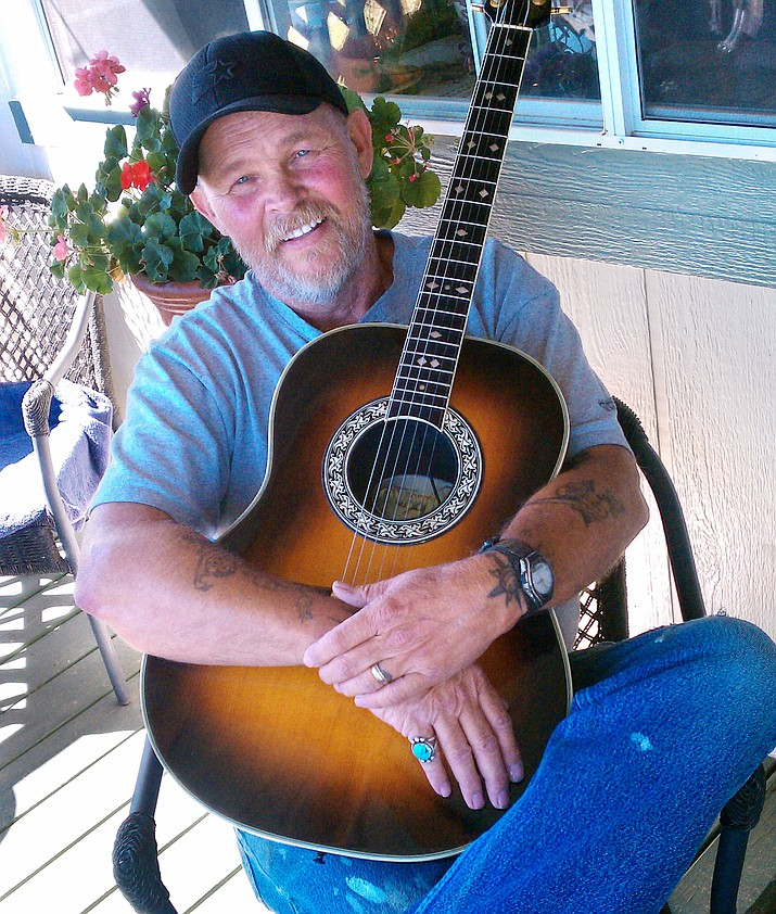 """I don't call myself a guitar player,"" said Jim Greenwood as he sits on the front porch of his Dewey, Arizona home."