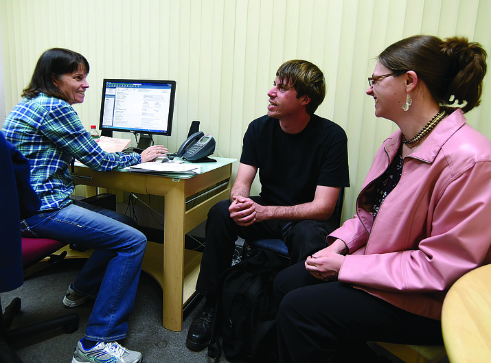 Lydia and Sean Watts laugh with Grace Barber, a Volunteer Quality Reviewer and Site Coordinator, during a free tax preparation service offered by Catholic Charities of Arizona, the Volunteer Income Tax Assistance program and the IRS. (Courier file photo)