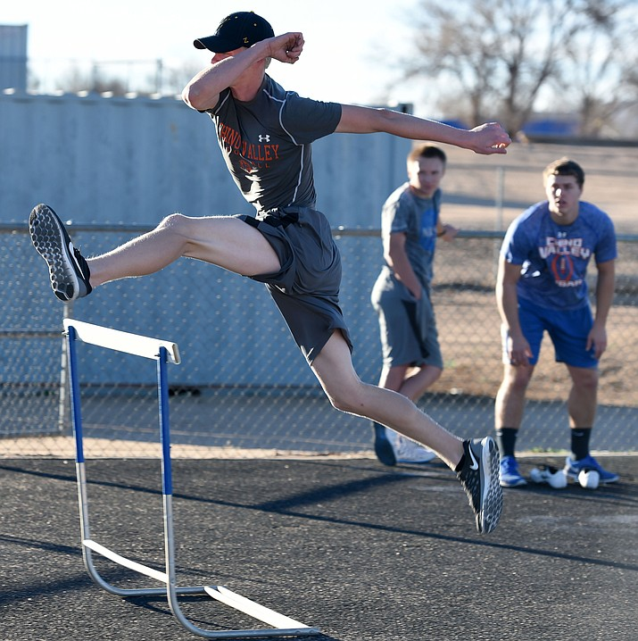 Chino Valley's Colton Sandberg practices his form leaping over hurdles Wednesday, Feb. 17, during team practice at CVHS.