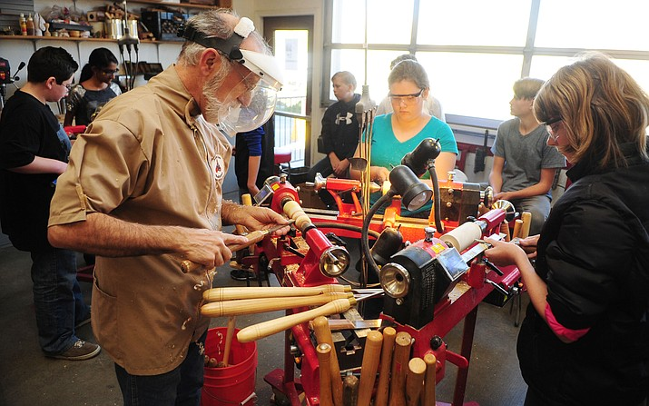 Courier file photo of Gary Frank of Prescott Area Woodturners showing students at Franklin Phonetic School how to make a snowman on a lathe.