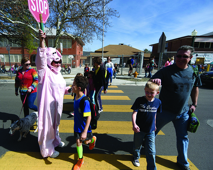 Lincoln Elementary School Principal Karen Hughes dressed in a pig costume escorts parents and students across a crosswalk Wednesday afternoon in Prescott. Students at Lincoln Elementary read over 1,000 minutes exceeding their goal for National Read Across America Day and having Principal Hughes dress up in a pig outfit.
