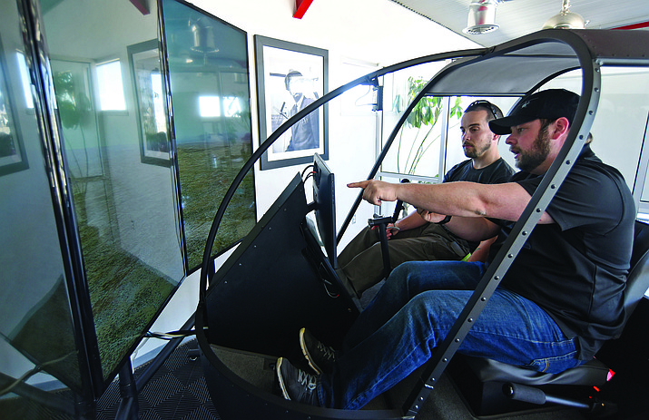 Guidance Aviation's Adam Pasquarella, right, with Student Services works with Ryan Bertucci, an Embry-Riddle Aeronautical University engineering student, on their new helicopter simulator Friday afternoon at the Prescott Airport.
