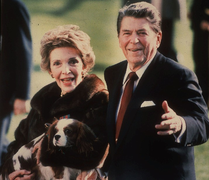 This December 1986 file photo shows first lady Nancy Reagan holding the Reagans' pet Rex, a King Charles spaniel, as she and President Reagan walk on the White House South lawn. The former first lady died Sunday, March 6, 2016 at age 94.