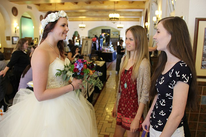 Emily McGrane, right, and Emily Bowen talk to Meagan Barker about the dress she's modeling for Formally Yours, a Prescott-based bridal and formal wear boutique, at the 2016 Prescott Bridal Affaire Expo.