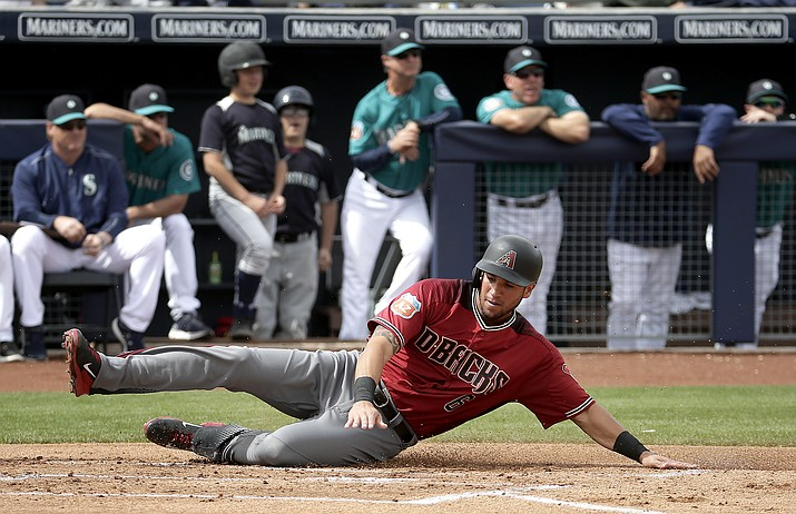 Diamondbacks' David Peralta slides home to score on a two-run double by Welington Castillo during their spring game against the Seattle Mariners on Monday, March 7, in Peoria.