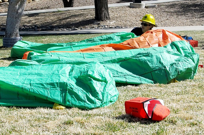 Five-year Forest Service Fire veteran Katie Markey checks on students in their fire shelters during the S130/190 Basic Wildland Firefighting class at the Arizona Wildfire Academy in Prescott Tuesday afternoon. (Loretta Benavidez/Courtesy photo)