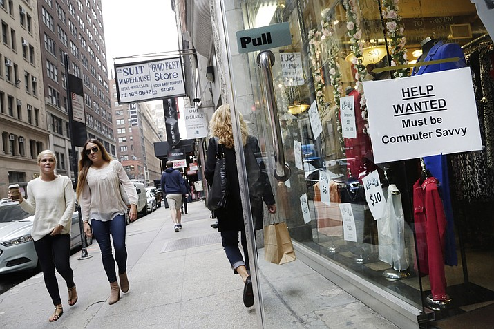 "In this file photo, a ""Help Wanted"" sign hangs in a store window in New York."