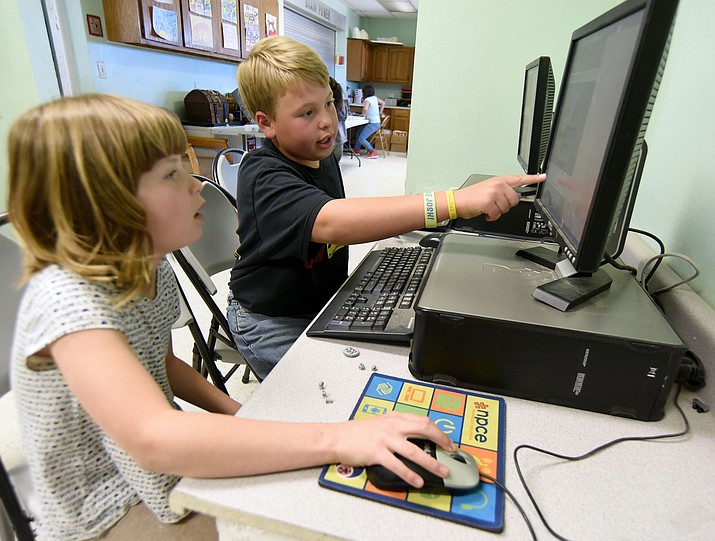 Gavin Obermeyer, 10, helps Graycie Handley, 9, program her Lego Mindstorm Robot on a PC Thursday afternoon at the Prescott Valley Boys and Girls Club. (Matt Hinshaw/The Daily Courier)
