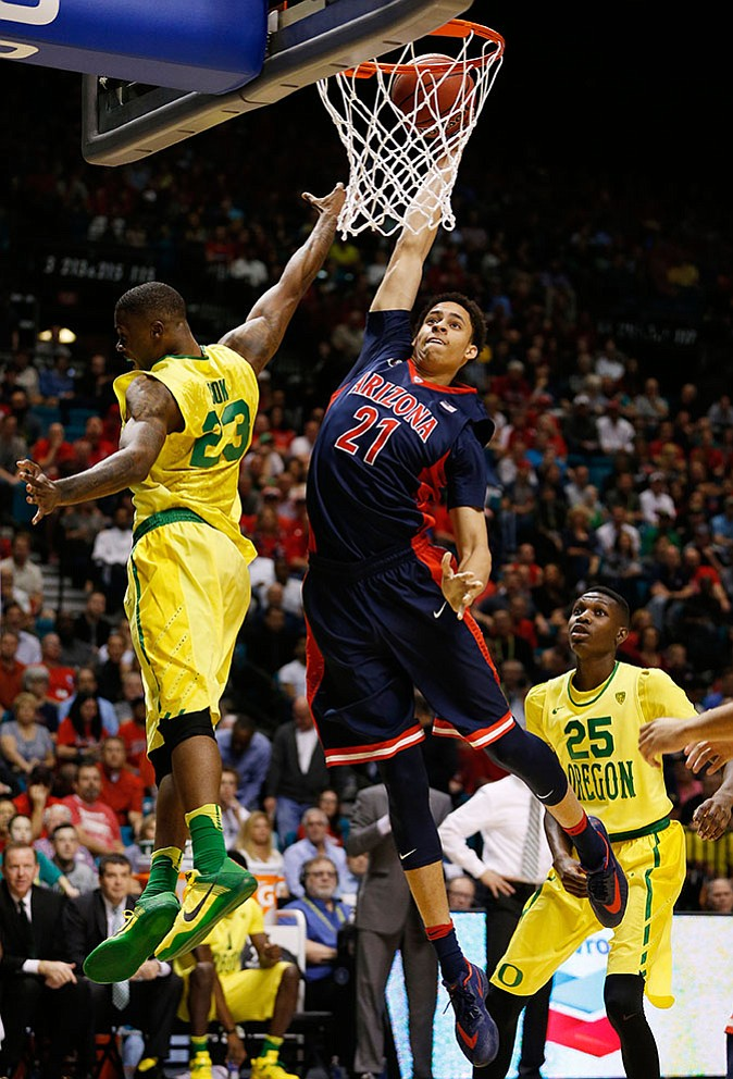 Arizona center Chance Comanche dunks over Oregon forward Elgin Cook, left, during their  game in the semifinal round of the Pac-12 men's tournament Friday, March 11, in Las Vegas.
