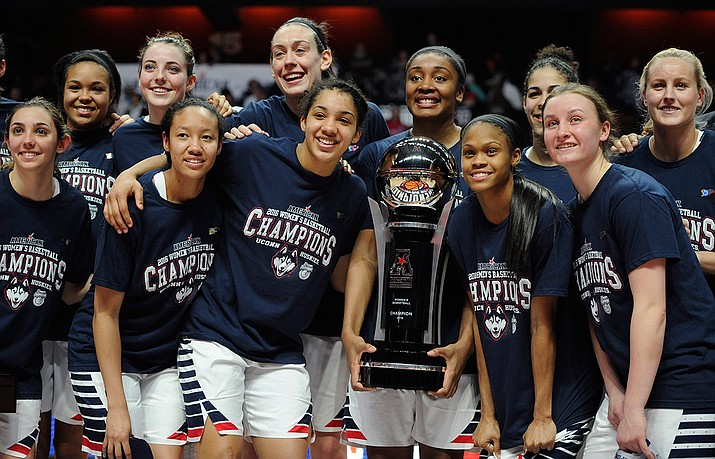Connecticut players pose with the championship trophy March 7 after beating South Florida in the American Athletic Conference tournament finals. UConn is the top overall seed in the women's NCAA tournament.