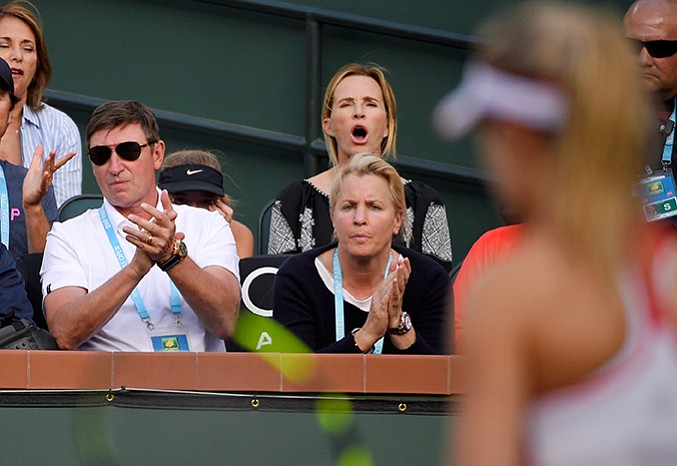 Former hockey player Wayne Gretzky, left, and his wife Janet Jones, top center, watch Eugenie Bouchard, right, of Canada, play Timea Bacsinszky, of Switzerland, at the BNP Paribas Open tennis tournament, Monday, March 14, in Indian Wells, Calif. Bacsinszky won 6-2, 5-7, 6-2.