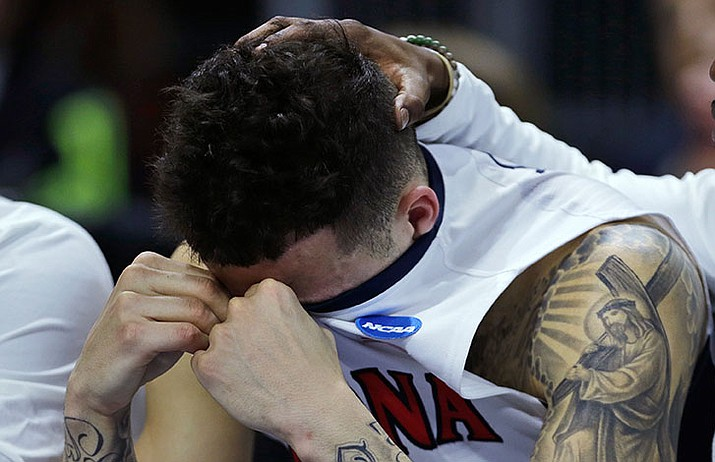 Arizona guard Gabe York hides his emotions as a teammate rests his hand on his head in the closing minute against Wichita State during the first round of the NCAA college men's basketball tournament in Providence, R.I., Thursday, March 17. Wichita State defeated Arizona 65-55.