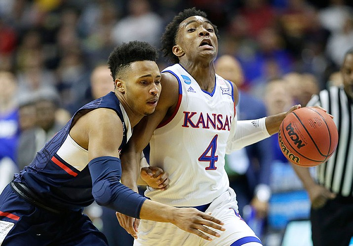 Kansas guard Devonte' Graham is fouled by Connecticut guard Jalen Adams after stealing the ball during their second-round men's college basketball game in the NCAA Tournament, Saturday, March 19, in Des Moines, Iowa.