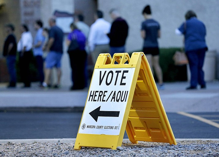 Voters wait in line to cast their ballot in Arizona's presidential primary election, Tuesday, March 22, in Phoenix.