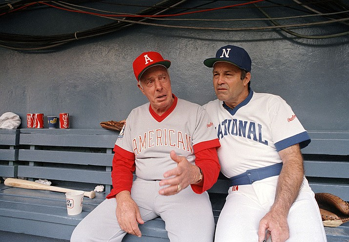Joe DiMaggio, left, and Joe Garagiola,  chat in the dugout on July 18, 1983, at Robert F. Kennedy Stadium in Washington, D.C., during warm ups for the second annual Cracker Jack Old Timers baseball game. A former big league catcher and popular broadcaster, Garagiola has died. He was 90.