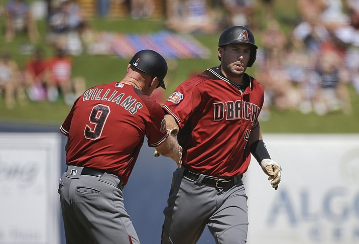Arizona Diamondbacks' Paul Goldschmidt, right, celebrates his home run with third base coach Matt Williams during the first inning of a spring training baseball game against the Milwaukee Brewers, Saturday, March 26, in Phoenix.
