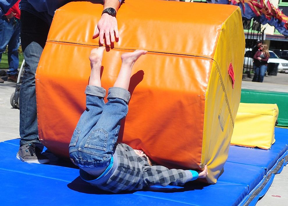 Brody Scott, four from Phoenix, goes tumbling in the Flip City Gymnastics obstacle course during the Great Prescott Easter Egg Hunt Saturday morning on the Yavapai County Courthouse Plaza.(Les Stukenberg/The Daily Courier)