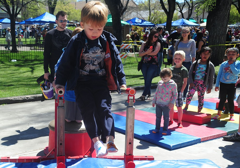 Jonas Parent handles the parrallel bars in the Flip City Gymnastics obstacle course during the Great Prescott Easter Egg Hunt Saturday morning on the Yavapai County Courthouse Plaza.(Les Stukenberg/The Daily Courier)