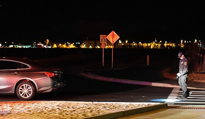 Prescott Valley Police Officer Matthew Cahill, an accident reconstructionist, inspects a crosswalk where two men were hit on April 1 at the intersection of Lake Valley Road and Lakeshore Drive in Prescott Valley.