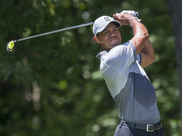 In this Saturday, Aug. 22, 2015 file photo, Tiger Woods tees off on the second hole during the third round of the Wyndham Championship golf tournament at Sedgefield Country Club in Greensboro, N.C.