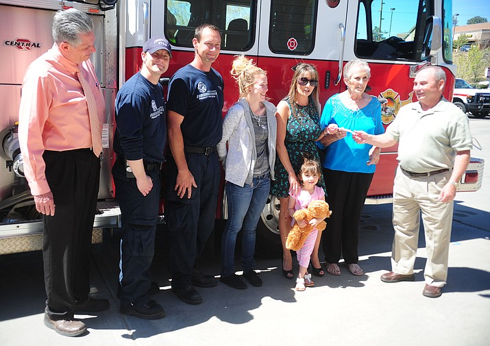 Prescott Firefighter Charities' Ron Kayser presents $500 to Regina Kaiser, Addison Perry, Briar Perry and Judy Laurvick after the family lost their home in a fire last month. Also pictured, from left, are Prescott Fire Chief Dennis Light, firefighter Jeremy Sarge and Captain Dan Bauman.  (Les Stukenberg/The Daily Courier)