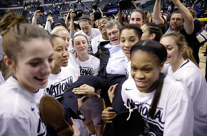 Connecticut head coach Geno Auriemma is carried off the court by members of his team after defeating Syracuse 82-51 in the NCAA women's championship game Tuesday, April 5, in Indianapolis.
