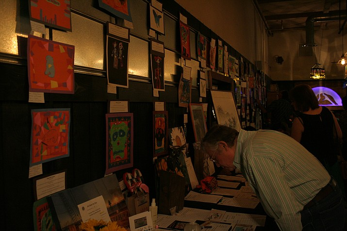 Howard McCullough looks over items in the silent auction at La Tierra Community School's fundraiser Sunday, April 3, at Granite Mountain Brewing in Prescott. The event showcased art by each of the school's students and raised funds to support music, foreign language and visual arts programs at the public charter school.