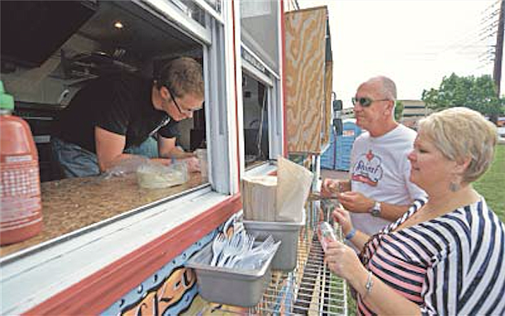 Mike Godina, co-owner of Gringo Dillas food truck from Flagstaff, takes Linda and Eric Oldham's orders during the first Prescott Food Truck Festival at Mile High Middle School in September 2015.