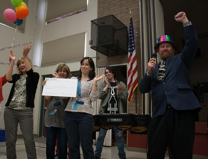 Superintendent Joe Howard, right, celebrates the delivery of checks to Prescott Unified School District teachers.