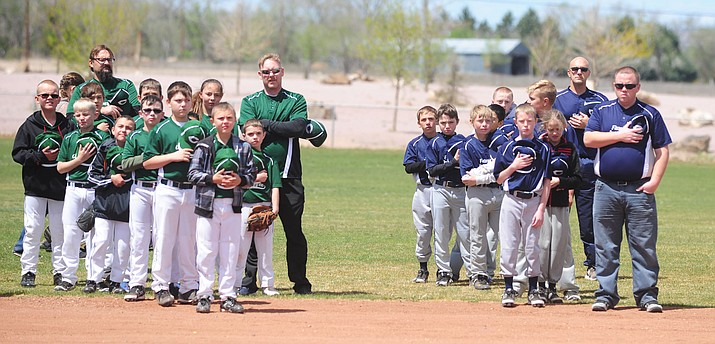 Players and coaches show respect as the National Anthem is played during opening ceremonies for the Chino Valley Little League Saturday afternoon.  (Les Stukenberg/The Daily Courier)