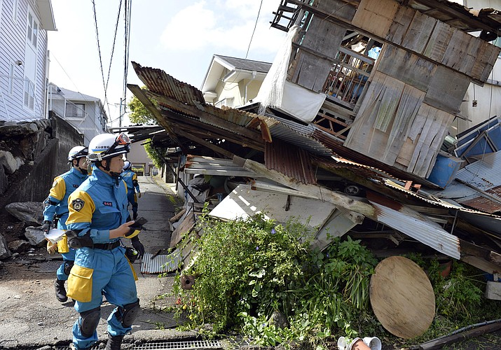 Police officers conduct a search operation at an earthquake-damaged house in Mashiki, Kumamoto prefecture, Japan Sunday, April 17. After two nights of earthquakes, flattened houses and triggered major landslides in southern Japan, 91,000 people had evacuated from their homes, according to a Kumamoto prefectural official.