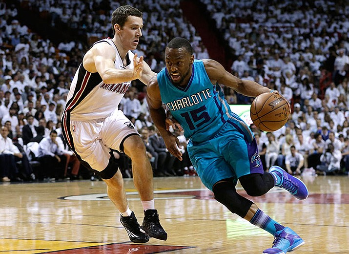 Charlotte Hornets guard Kemba Walker drives to the basket as Miami Heat guard Goran Dragic defends during their game Sunday, April 17, in Miami.