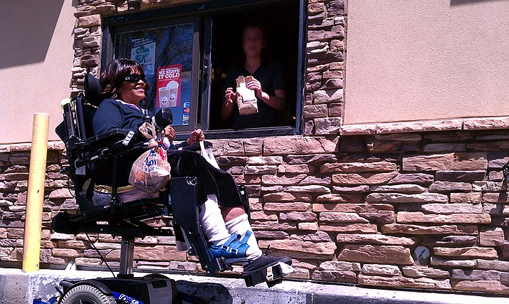 Severely disabled and facing life alone from day to day, the only reasonable way Marquette can independently enjoy a fast food meal is to take her wheelchair through the drive-through window lane of restaurants like the Prescott Valley Burger King -- something that is officially against Burger King corporate policy. (I've blurred the employee's face to protect them from corporate disciplinary action.)