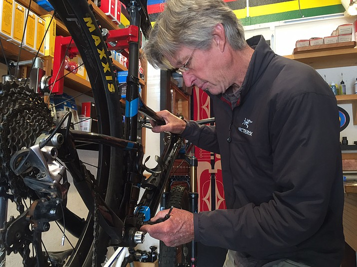 Southwest Sounds & Cyclery owner Ed Furbush adjusts the gear ratio on a $7,000 mountain bicycle a local rider intends to use for the Whiskey Off-Road.