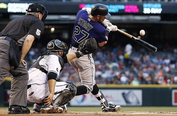 Colorado Rockies' Trevor Story (27) fouls off a pitch as Arizona Diamondbacks' Welington Castillo, center, and umpire Paul Emmel (5) look on during the first inning of a baseball game Friday, April 29, in Phoenix.
