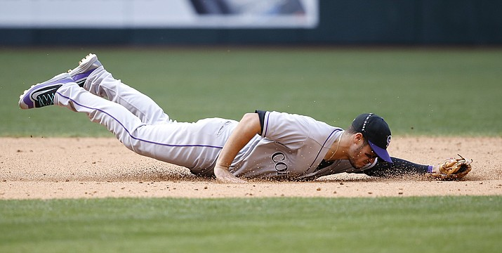 Colorado Rockies' Nolan Arenado dives for but is unable to come up with a ground ball hit by Arizona Diamondbacks' Chris Herrmann during the sixth inning Sunday, May 1, in Phoenix.
