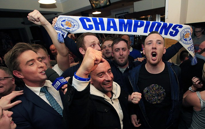 Leicester City fans celebrate in the Market Tavern in Leicester after seeing their side crowned English Premier League soccer champions following Tottenham Hotspur's 2-2 draw against Chelsea. The match resulted in Leicester City winning the Premier League, Monday, May 2.