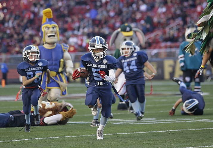 San Jose Marauders youth football players play against sports mascots during halftime of a 2015 NFL football game between the San Francisco 49ers and the Arizona Cardinals in Santa Clara, Calif. The first concussion study of its kind found youth football players are more likely to return to play less than a day after injury, compared to those in high school and college.