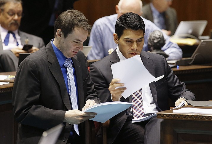 Rep. J.D. Mesnard, left, R-Chandler, talks with Rep. Steve Montenegro, R-Avondale, in the House during budget deliberations at the Arizona Capitol, Tuesday, May 3, in Phoenix. The Legislature gave final approval to the state budget early Wednesday.