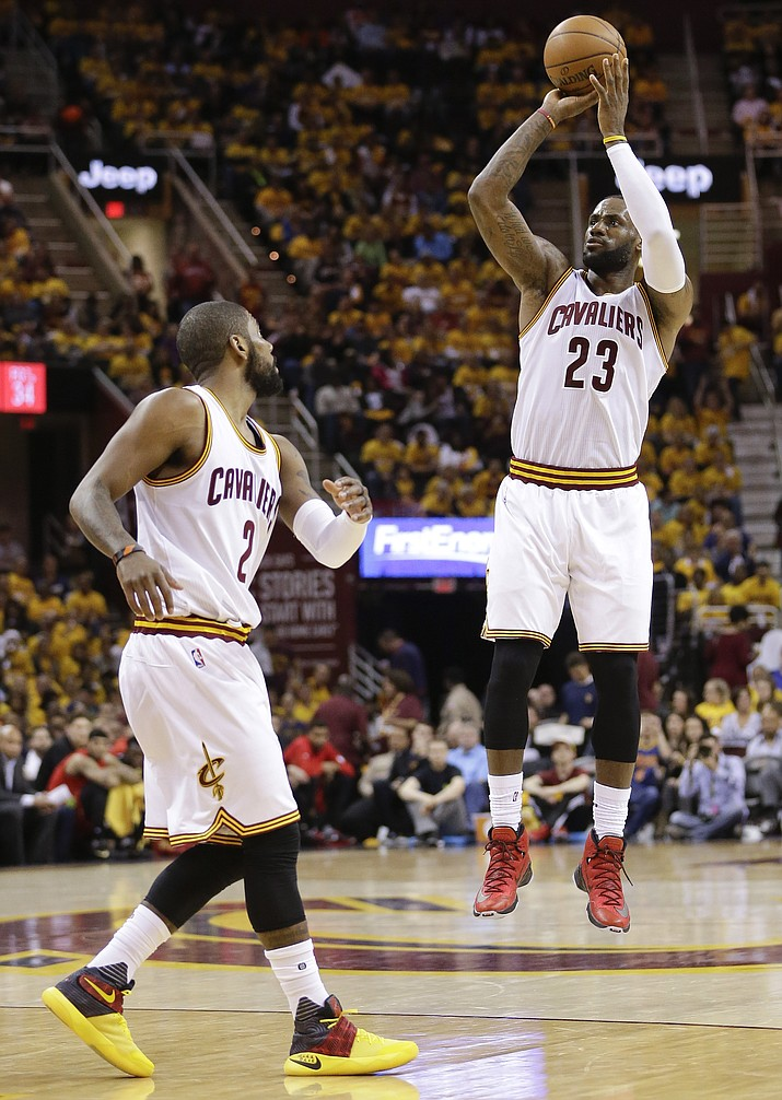 Cleveland Cavaliers forward LeBron James puts up a 3-point shot as guard Kyrie Irving looks on in the second half against the Atlanta Hawks during Game 2 of a second-round NBA basketball playoff series, Wednesday, May 4, in Cleveland.