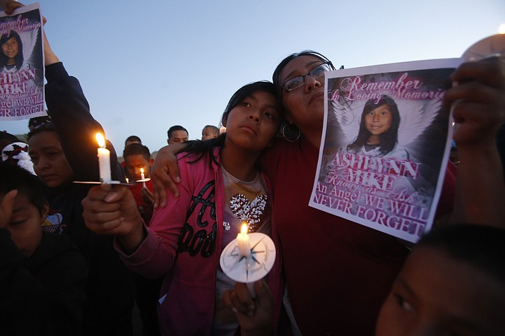 This Tuesday, May 4, 2016 photo Klandre Willie, left, and her mother, Jaycelyn Blackie, participate in a candlelight vigil, for Ashlynne Mike at the San Juan Chapter House in Lower Fruitland, N.M. The FBI said Mike, was abducted after school on Monday and her body was found the next day. Tom Begaye was arrested in connection with Mike's disappearance and death.