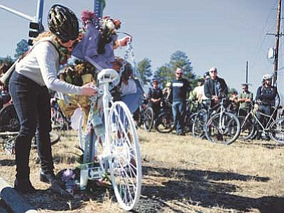 """Lisa Zander locks up the """"ghost bike"""" after over 100 bicyclists participated in a memorial ride for Amber """"Cricket"""" Harrington from Prescott College to the intersection of Copper Basin and White Spar Road where Harrington died. At the intersection a """"ghost bike"""" was placed to remember Harrington."""