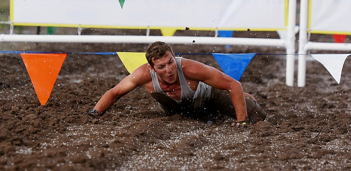 Sean DalCerro crawls under an obstacle as the hail pelts down during the Chino Mudder that is part of the Extreme Spring Fling in Chino Valley Saturday morning. (Les Stukenberg/The Daily Courier)