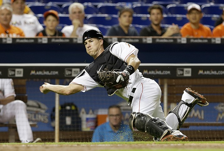 Miami Marlins catcher J.T. Realmuto prepares to throw to home plate after fielding a wild pitch in the fourth inning of a baseball game against the Milwaukee Brewers, Tuesday, May 10, in Miami. Jonathan Villar was safe at home plate.